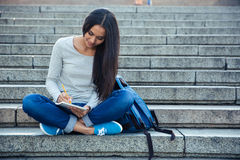 Happy female student writing notes in notepad Stock Photo