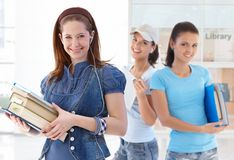 Happy female students in library lobby Royalty Free Stock Photos