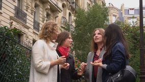 Happy female students talking outside in slow motion near university building. Gladden female students standing near university building and speaking in slow stock video footage