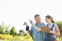 Happy female supervisor explaining something to gardener at plant nursery Stock Photos