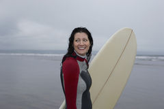 Happy Female Surfer With Surfboard Looking Away At Beach Royalty Free Stock Photos