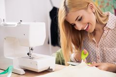 Happy female tailor cutting cloth Royalty Free Stock Images