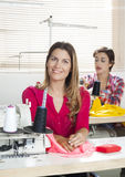 Happy Female Tailor Sitting At Workbench. Portrait of happy female tailor sitting at workbench in sewing factory with colleague in background Royalty Free Stock Image