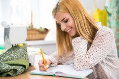 Happy female tailor writing notes Royalty Free Stock Photos