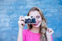 Happy female taking photo on retro vintage hipster camera. Royalty Free Stock Image