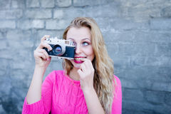 Happy female taking photo on retro vintage hipster camera. Royalty Free Stock Images