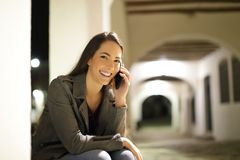 Happy female talking on phone looking at you. Sitting in the street in the night royalty free stock image