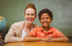 Happy female teacher and boy in classroom. Portrait of happy female teacher and little boy in the classroom Royalty Free Stock Images