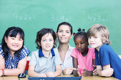 Happy female teacher with her multirace classroom at school desk Royalty Free Stock Image