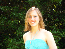 Happy female teen in dress. Portrait of smiling female teenager with turquoise dress outdoors, green leaves in background Stock Photo