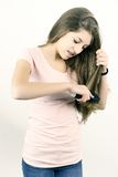 Happy female teenager combing long hair Royalty Free Stock Photo