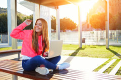 Happy female teenager greeting hello while sitting with open laptop outdoors Stock Image