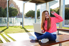 Happy female teenager greeting hello while sitting with open laptop outdoors Stock Images