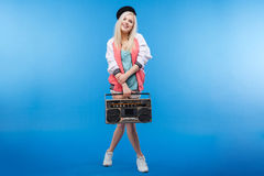 Happy female teenager holding retro boom box Stock Photos