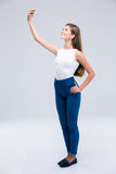 Happy female teenager making selfie photo on smartphone Royalty Free Stock Photo