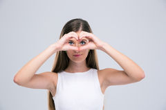 Happy female teenager showing heart gestur. Portrait of a happy female teenager showing heart gesture with fingers and looking at camera isolated on a white Stock Photo