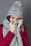 Happy female teenager smiling in hiding herself under winter scarf Royalty Free Stock Photos