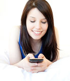 Happy female teenager using cellphone on the bed Stock Photos