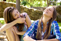 Happy female teenagers laughing having fun in park in summer Royalty Free Stock Photos