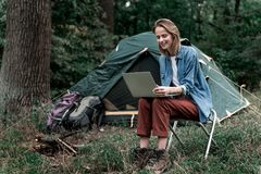 Happy female tourist entertaining with notebook in the woods Stock Image