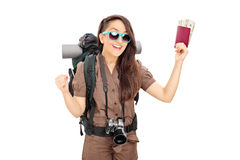 Happy female tourist holding passport with money. Isolated on white background stock photo