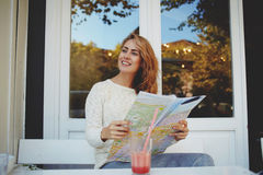 Happy female tourist with location map in hands sitting in comfortable sidewalk cafe during weekend relaxation, Royalty Free Stock Images
