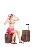 Happy female tourist sitting on her luggage Stock Images