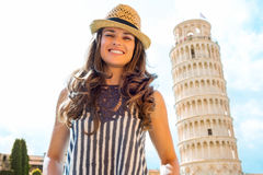 Happy female tourist smiling near Leaning Tower of Pisa. A lovely brunette wearing a straw hat smiles happily. In the background, the leaning tower of Pisa Stock Photography