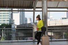 Happy female tourist with suitcase exploring map while standing. In city building Royalty Free Stock Image