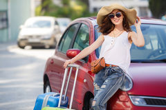 Happy female tourist with suitcases near the car. Big straw hat,dark sunglasses,suitcases on wheels is a lovely woman with a beautiful smile, in a white top and Stock Photos
