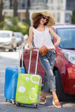 Happy female tourist with suitcases near the car. Big straw hat,dark sunglasses,suitcases on wheels is a lovely woman with a beautiful smile, in a white top and Royalty Free Stock Images