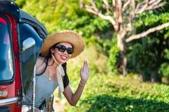 Happy female tourist in a tuk tuk. On Asia trip woman tuktuk asian rickshaw vehicle girl bangkok pretty outdoors window vietnam transport beautiful tuk-tuk royalty free stock photos