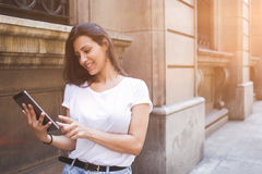 Happy female tourist is using touch pad for navigation during her summer vacation trip Stock Image