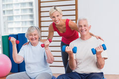 Happy female trainer with senior couple Stock Photos