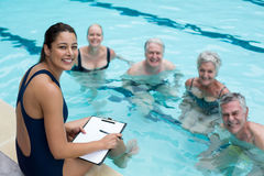 Happy female trainer and senior swimmers. Portrait of happy female trainer and senior swimmers Stock Photography