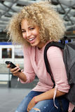 Happy female traveler with backpack and phone Royalty Free Stock Images