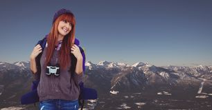 Happy female traveler carrying backpack on mountain against clear sky Stock Images