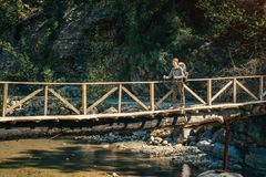 Hiker on the wooden bridge over mountain river in Turkey Royalty Free Stock Photos