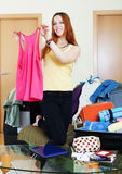 Happy female traveler packing suitcase Stock Photo
