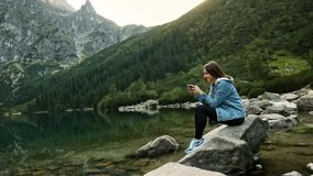 Happy female traveler playing a mobile game on cellphone on a mountain lake, resting on nature. At sunset stock video
