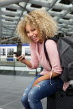 Happy female traveler sitting on suitcase with cell phone Stock Image