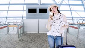 Female traveler uses cellphone in airport. Happy female traveler standing in the airport hall while using a mobile phone with her suitcase stock video footage