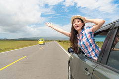 Happy female traveler stuck out car window Royalty Free Stock Image