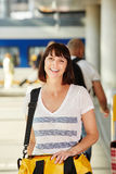 Happy female traveler walking in train station with bag Royalty Free Stock Photography