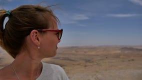Happy female traveller enjoying desert view from cliff`s edge stock video