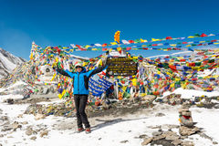 Happy female trekker celebrating ascend to Thorong La pass. Happy female trekker celebrating ascend to Thorong La pass at 5416m. Annapurna circuit trek in Nepal royalty free stock photo