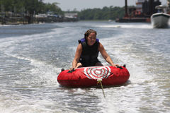 Happy Female tubing. A female tubing in the water stock image