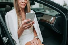 Happy female typing in mobile in car Royalty Free Stock Photo
