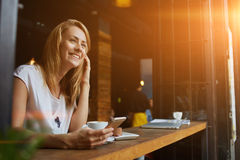 Happy female using smart phone while relaxing in cafe after walking during her summer weekend Stock Photography