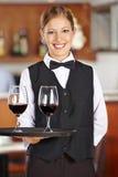 Happy female waiter with wine glasses royalty free stock photo